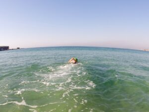 A solo swimmer swimming away from the beach, out to sea.